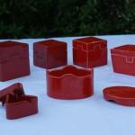 Boîtes rouges vifs et rouges foncées,entièrement montées à la main, en faience blanche.