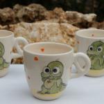 Tasse pour enfant en faïence blanche,décorée de deux bébés dragons et des petits coeurs de couleur à l'intérieur